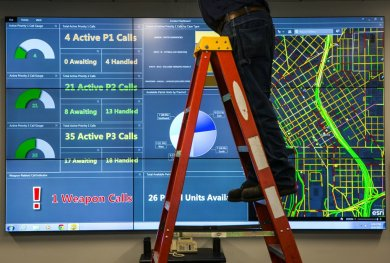 A maintenance worker puts the finishing touches on the Seattle Police Department's new Real Time Crime Center at their headquarters in Downtown Seattle Tuesday, October 6, 2015. The new system will help Seattle Police track crime and find trends as they happen, to help the department to be more responsive.